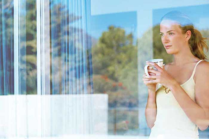 Lady standing near a window with the mug in her hands